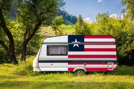 A car trailer, a motor home, painted in the national flag of Liberia stands parked in a mountainous. The concept of road transport, trade, export and import between countries. Travel by car