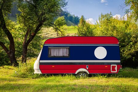 A car trailer, a motor home, painted in the national flag of Laos stands parked in a mountainous. The concept of road transport, trade, export and import between countries. Travel by car