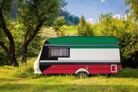 A car trailer, a motor home, painted in the national flag of Kuwait stands parked in a mountainous. The concept of road transport, trade, export and import between countries. Travel by car