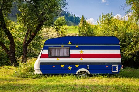 A car trailer, a motor home, painted in the national flag of Cape Verde stands parked in a mountainous. The concept of road transport, trade, export and import between countries. Travel by car