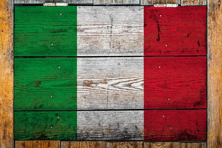 National flag of Italy on a wooden wall background.The concept of national pride and symbol of the country.Flag painted on a wooden fence with metal nails.