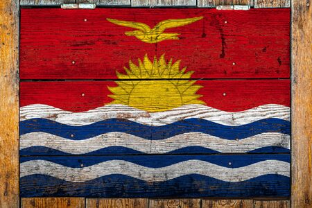 National flag of Kiribati on a wooden wall background.The concept of national pride and symbol of the country.Flag painted on a wooden fence with metal nails.