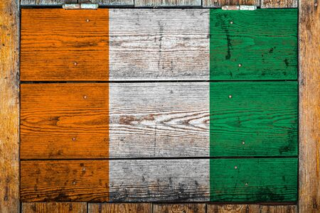 National flag of Cote divoire on a wooden wall background.The concept of national pride and symbol of the country.Flag painted on a wooden fence with metal nails. 版權商用圖片