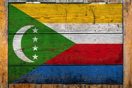 National flag of Comoros on a wooden wall background.The concept of national pride and symbol of the country.Flag painted on a wooden fence with metal nails.