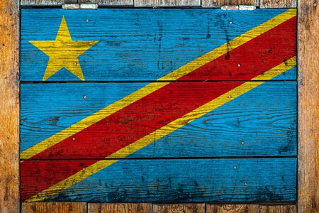 National flag of Democratic Republic of the Congo on a wooden wall background.The concept of national pride and symbol of the country.Flag painted on a wooden fence with metal nails.
