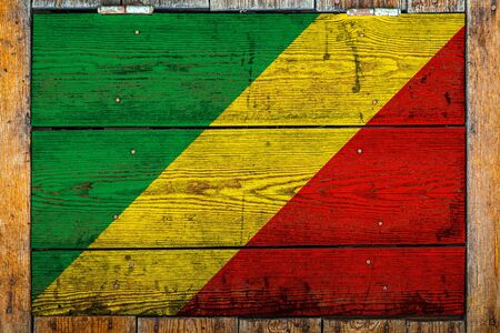 National flag of Republic of the Congo on a wooden wall background.The concept of national pride and symbol of the country.Flag painted on a wooden fence with metal nails.