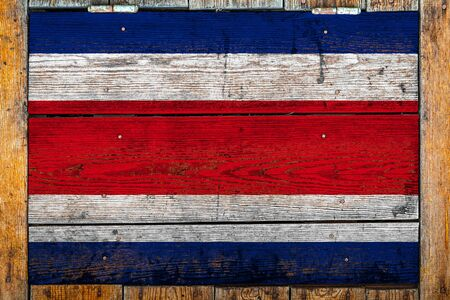 National flag of Costa Rica on a wooden wall background.The concept of national pride and symbol of the country.Flag painted on a wooden fence with metal nails.