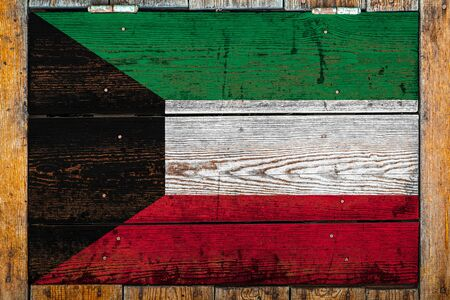 National flag of Kuwait on a wooden wall background.The concept of national pride and symbol of the country.Flag painted on a wooden fence with metal nails.