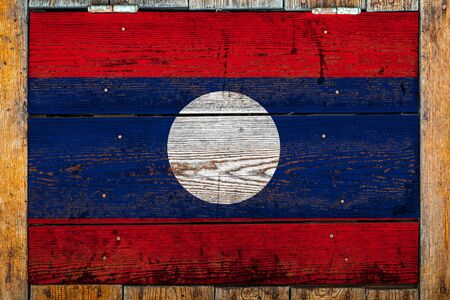 National flag of Laos on a wooden wall background.The concept of national pride and symbol of the country.Flag painted on a wooden fence with metal nails.