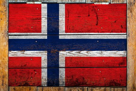 National flag of Norway on a wooden wall background.The concept of national pride and symbol of the country.Flag painted on a wooden fence with metal nails.