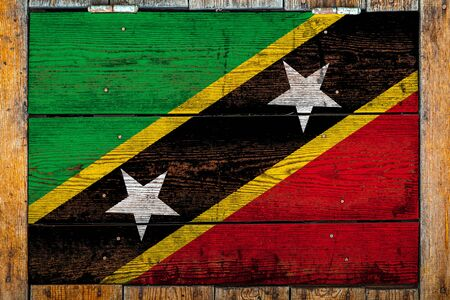 National flag of Saint Kitts and Nevis on a wooden wall background.The concept of national pride and symbol of the country.Flag painted on a wooden fence with metal nails.