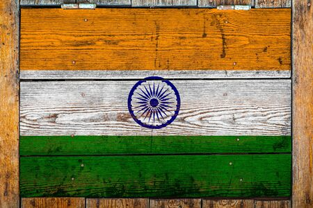 National flag of India on a wooden wall background.The concept of national pride and symbol of the country.Flag painted on a wooden fence with metal nails.