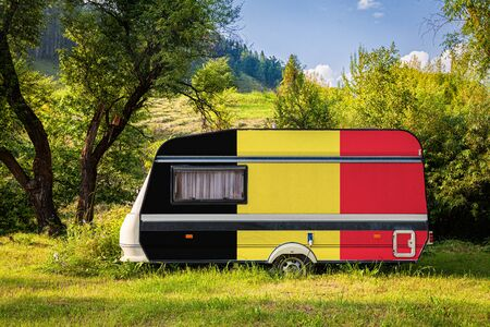 A car trailer, a motor home, painted in the national flag of  Belgium stands parked in a mountainous. The concept of road transport, trade, export and import between countries. Travel by car