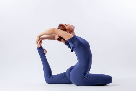 Young athletic woman gymnast in gymnastic jumpsuit does stretching in difficult poses on a white-lined background. The concept of female beauty, sport and grace.