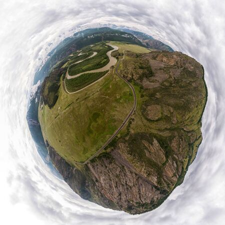 Helicopter drone shot. Aerial photography of a mountain,  green field, road, small village and forest. Panoramic city 360  shot from above