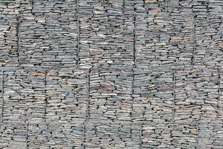 A wall lined with small gray stones behind a metal grate so that the mountains do not crumble. Stone texture Фото со стока