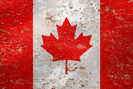 National flag of Canada  on old peeling wall background.The concept of national pride and symbol of the country. Zdjęcie Seryjne