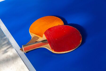 Close-up of two red and orange table tennis rackets lying on a blue table Фото со стока