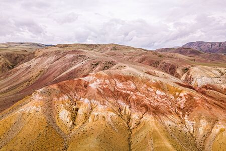 A stunning panorama of a mountain chain of peaks, a canyon with red clay, top view. Mars fields in Altai, Russia