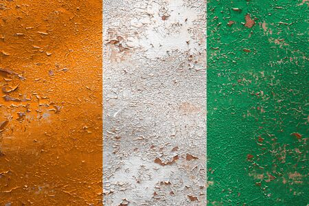 National flag of Cote divoire on old peeling wall background.The concept of national pride and symbol of the country.