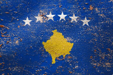 National flag of Kosovo on old peeling wall background.The concept of national pride and symbol of the country.