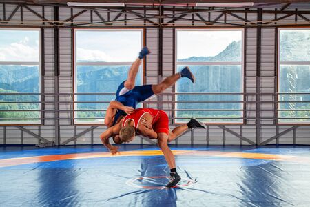 Two young men in blue and red wrestling tights are wrestlng and making shot through the thigh on a  blue wrestling carpet in the gym on the background of mountains. The concept of male wrestling and resistance Zdjęcie Seryjne