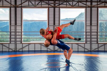 Two young men in blue and red wrestling tights are wrestlng and making a suplex wrestling on a  blue wrestling carpet in the gym on the background of mountains. The concept of male wrestling and resistance