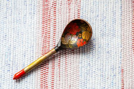 Old Russian traditional wooden spoon lie on an old traditional carpet. Russian traditions. Decorated with wooden spoons with a vegetable pattern 免版税图像