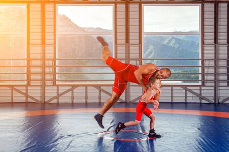 The little boy in sport tights wrestler throws over the hip adult male wrestler on a wrestling carpet in the gym. The concept of child power and martial arts training. Teaching children Greco-Roman wrestling