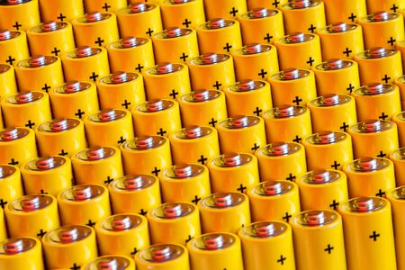Alkaline battery aa size. Several batteries in rows.A close-up of the same yellow batteries, lined up in even rows by positive charges. An unsafe way to use energy.