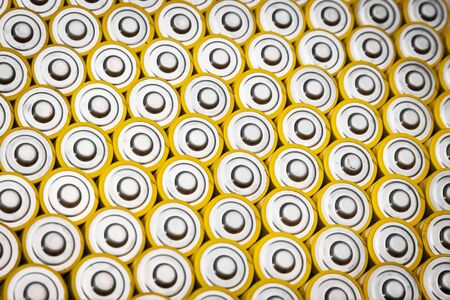 Close view of batteries alkaline 1.5 Volts in size AA Several batteries in rows.A close-up of the same yellow batteries, lined up in even rows by positive charges. An unsafe way to use energy.