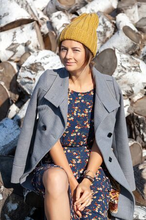 Portrait of a  cheerful woman in a knitted hat, coat, pretty dress and boots, smiles cute, poses, smiles and sits on birch logs. The concept of rustic style and life in ancient times Stockfoto