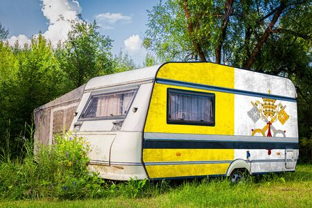 A car trailer, a motor home, painted in the national flag of  Vatican stands parked in a mountainous. The concept of road transport, trade, export and import between countries. Stock Photo