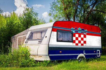 A car trailer, a motor home, painted in the national flag of  Croatia stands parked in a mountainous. The concept of road transport, trade, export and import between countries.