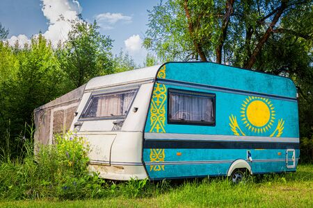 A car trailer, a motor home, painted in the national flag of  Kazakhstan stands parked in a mountainous. The concept of road transport, trade, export and import between countries.