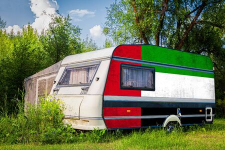 A car trailer, a motor home, painted in the national flag of  United Arab Emirates stands parked in a mountainous. The concept of road transport, trade, export and import between countries.