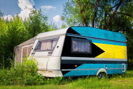 A car trailer, a motor home, painted in the national flag of  Bahamas stands parked in a mountainous. The concept of road transport, trade, export and import between countries. Stock Photo
