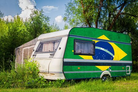 A car trailer, a motor home, painted in the national flag of South African Republic stands parked in a mountainous. The concept of road transport, trade, export and import between countries. Stock Photo