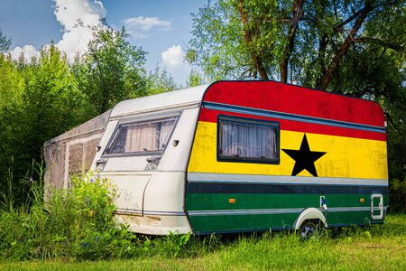A car trailer, a motor home, painted in the national flag of  Ghana stands parked in a mountainous. The concept of road transport, trade, export and import between countries. Stock Photo