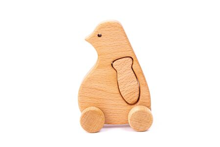 Photo of a wooden penguin with fish on wheels  of beech. Toy made of wood  on a white isolated background.A toy for entertaining children and resting parents