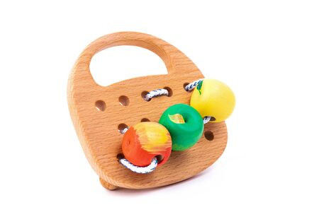 Photo of a wooden wooden toy with lace and beads of different colors on wheels  of beech. Toy made of wood  on a white isolated background.A toy for entertaining children and resting parents Standard-Bild - 129844576