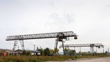 Two large metal gantry cranes at a construction site, in the background industrial warehouses for storing goods. Type of bearing metal structures of gantry crane against the blue sky