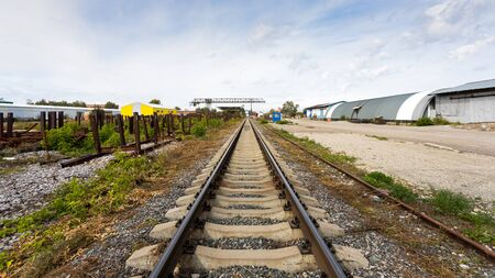 large plan railroad tracks against the background of a construction site, production workshop, warehouse, gantry crane. Industrial concept of transportation, loading and storage of goods Standard-Bild - 129844584