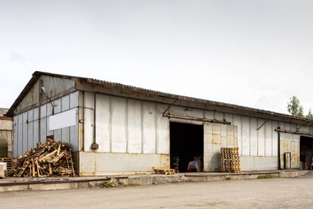 A large metal industrial warehouse for storing goods, next to it are wooden pallets for storing goods. Industrial concept of transportation, loading and storage of goods Standard-Bild - 129844585