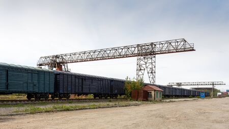 Large metal gantry cranes at a on the railway platform, standing on freight wagons for storing goods. Type of bearing metal structures of gantry crane against the blue sky