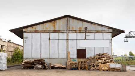 A large metal industrial warehouse for storing goods, next to it are wooden pallets for storing goods. Industrial concept of transportation, loading and storage of goods Standard-Bild - 129846760