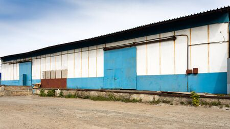 Facade on large industrial building made of metal white and blue panels. Industrial concept of transportation, loading and storage of goods Standard-Bild - 129846758