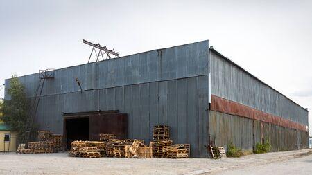 Façade d'un grand bâtiment industriel en panneaux gris métal, à côté se trouvent des palettes en bois pour le stockage des marchandises. Concept industriel de transport, chargement et stockage de marchandises