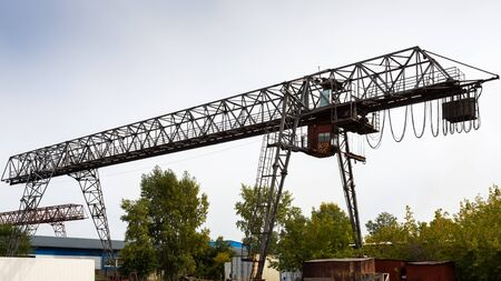 large metal gantry crane at a construction site, in the background industrial warehouses for storing goods. Type of bearing metal structures of gantry crane against the blue sky
