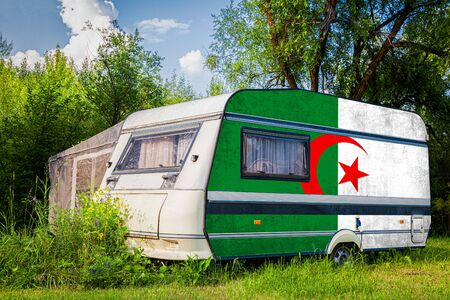 A car trailer, a motor home, painted in the national flag of  Algeria stands parked in a mountainous. The concept of road transport, trade, export and import between countries. Standard-Bild - 129846781